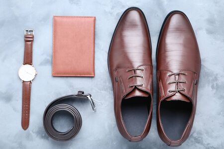 Male leather shoes with belt, passport and wrist watch on grey background Archivio Fotografico - 129154822