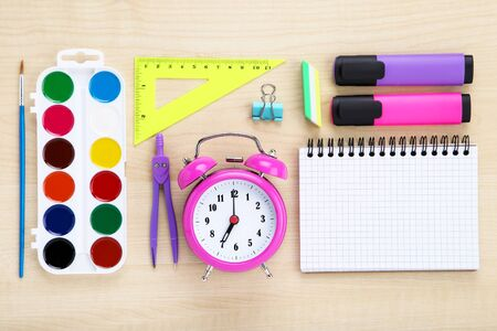 School supplies with pink alarm clock on brown wooden table