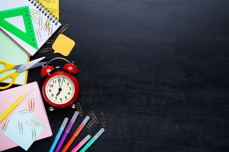 Different school supplies with alarm clock on blackboard