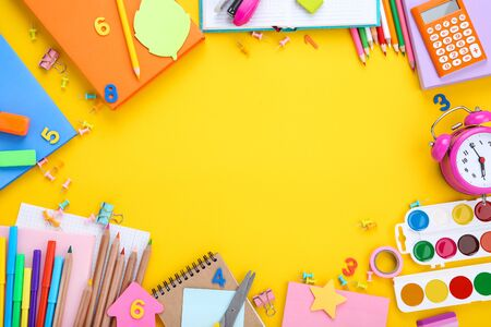 Different school supplies on yellow