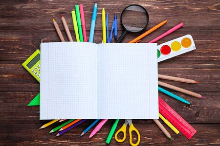 School supplies with opened notebook on brown wooden table
