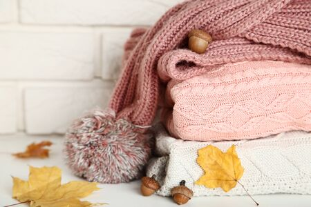 Stack of folded sweaters with scarf, acorns and autumn leafs on brick wall