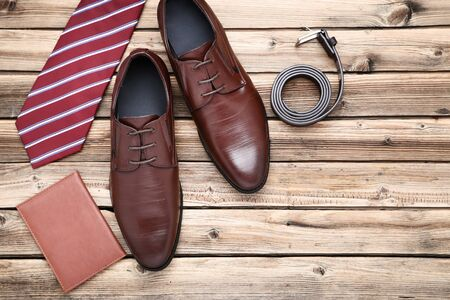 Male leather shoes with passport and accessories on brown wooden table Archivio Fotografico - 129153712