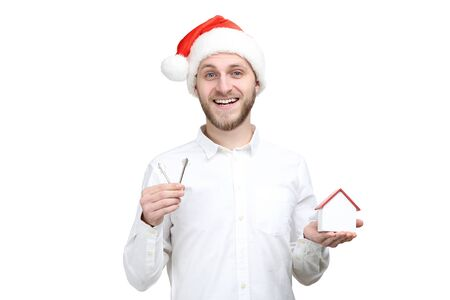 Young man with silver keys, santa hat and wooden house on white background 写真素材