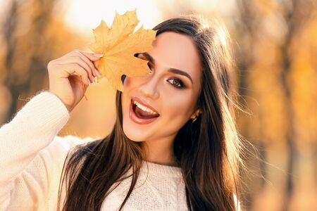 Beautiful woman holding maple leaf in autumn park
