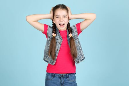Beautiful young girl closing ears by hands on blue background