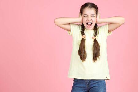 Beautiful young girl closing ears by hands on pink background Stok Fotoğraf