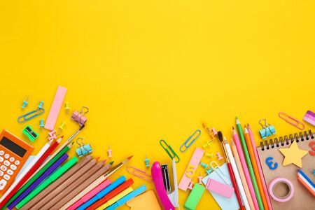 Different school supplies on yellow background