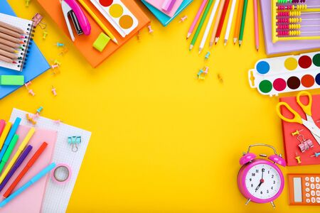 Different school supplies with alarm clock on yellow background