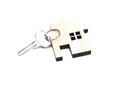 Silver key with wooden house isolated on white background 写真素材