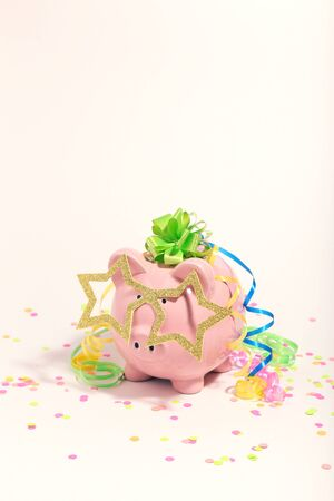 Piggybank with ribbons and confetti on white background. Minimalism concept Stock Photo