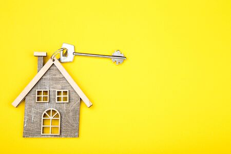Silver key with wooden house on yellow background