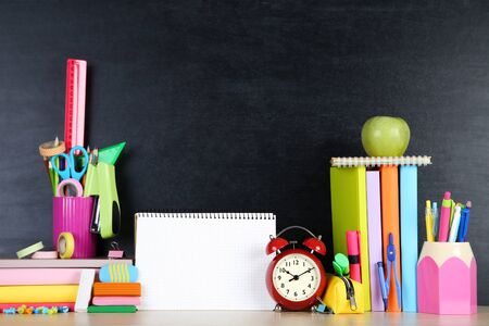 School supplies with blank sheet of paper on blackboard background