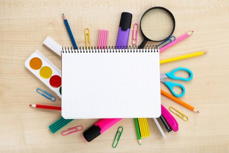 School supplies with blank sheet of paper on brown wooden table