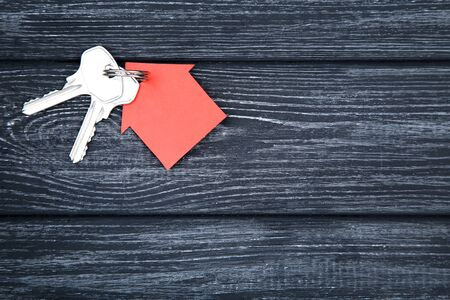 Silver keys with red paper house on black wooden table 写真素材
