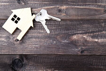 Silver keys with house symbol on brown wooden table 写真素材