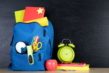 School supplies with blue backpack on blackboard background