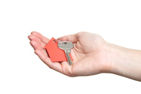 Female hand holding silver key with paper house on white background