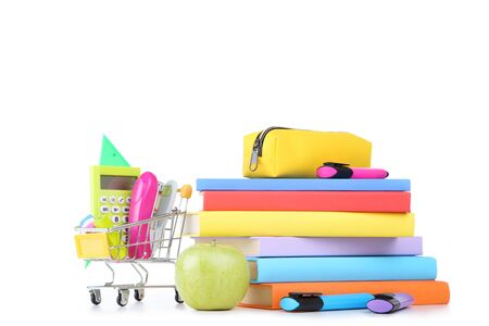 School supplies with stack of books and green apple on white background