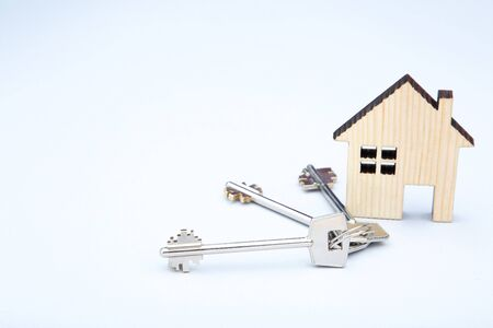 Silver keys with wooden house on grey background