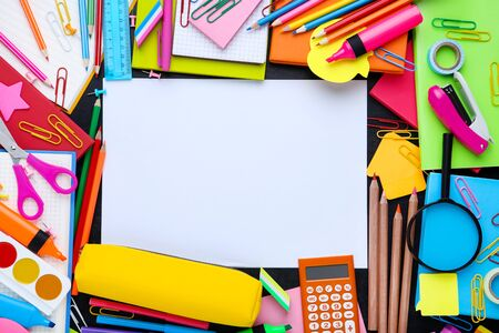 Different school supplies with blank sheet of paper on blackboard 写真素材