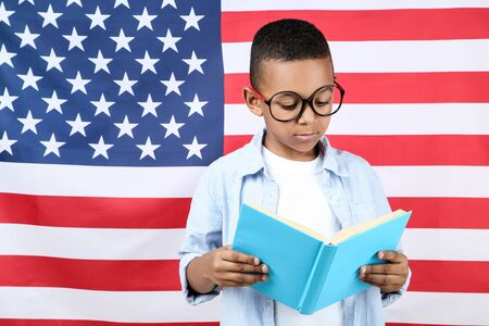 Cute boy with book on american flag background Banque d'images