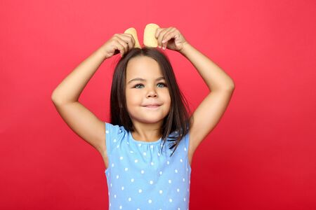 Beautiful little girl with potato chips on red background
