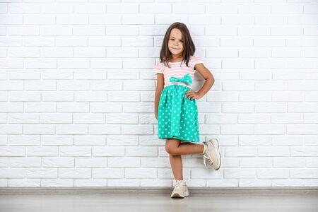 白レンガの壁の背景に美しい小さな女の子
