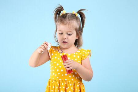 Cute little girl blowing soap bubbles on blue background