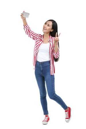 Young woman making selfie on smartphone on white background