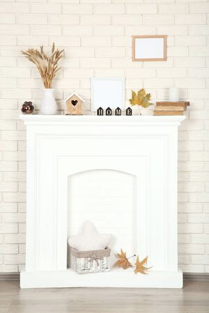White fireplace with photo frames, wheat ears and old books 写真素材