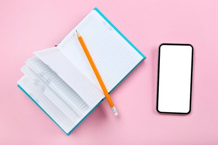 Smartphone with notepad and pencil on pink background Stock Photo