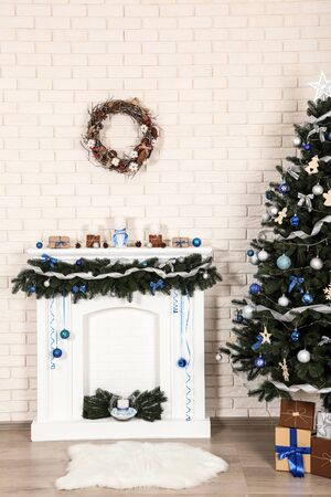 Decorated fireplace near christmas tree on brick wall background