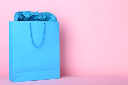 Paper shopping bag on pink background