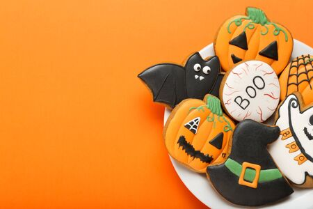 Halloween gingerbread cookies in plate on orange background Stock Photo