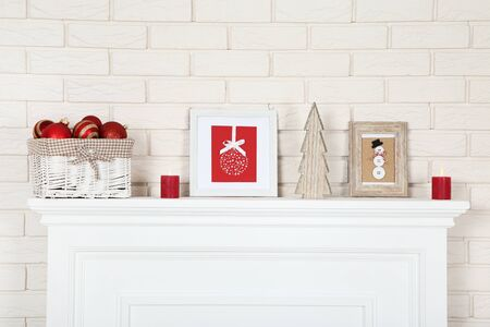 White fireplace with christmas ornaments, photo frames and wooden fir tree 写真素材