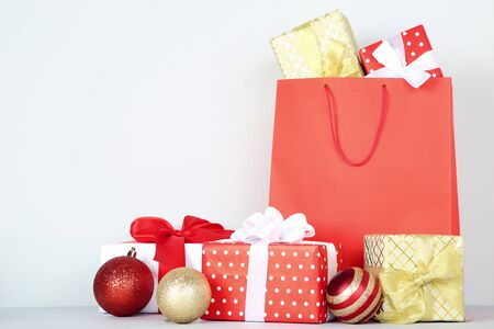 Shopping bag with gift boxes and christmas baubles on grey background