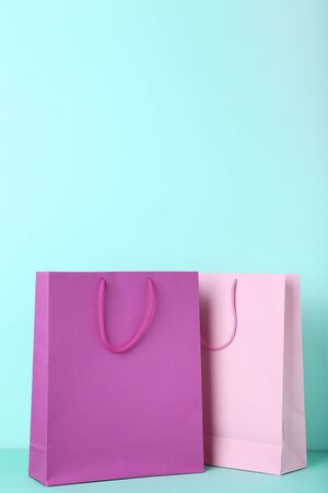 Colorful paper shopping bags on mint background 写真素材