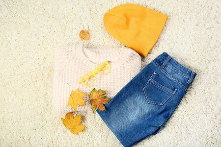 Knitted sweater with jeans, hat and maple leafs on white carpet