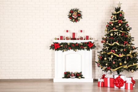 White decorated fireplace near christmas tree on brick wall background