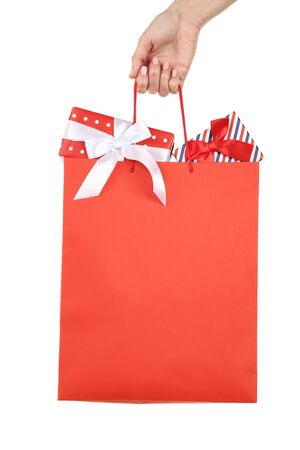 Female hand holding shopping bag with gift boxes on white background