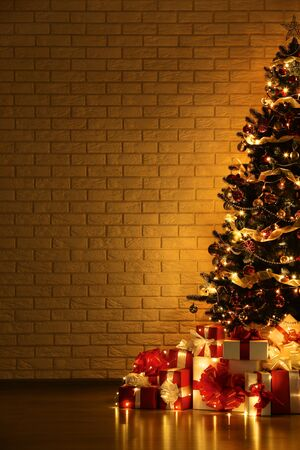 Christmas tree with decorations and gift boxes on brick wall background 写真素材