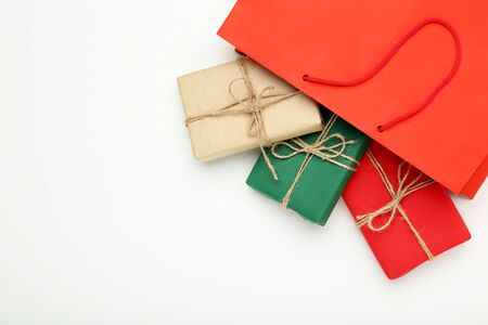 Shopping bag with gift boxes on grey background