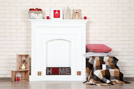 White fireplace with christmas ornaments, pillows and plaid