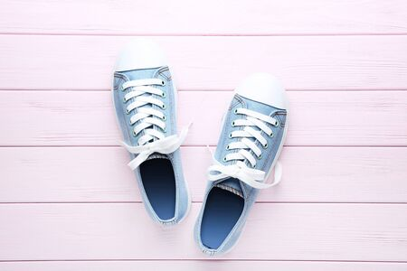 Pair of blue sneakers on pink wooden table