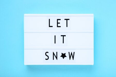 Lightbox with words Let It Snow on blue background