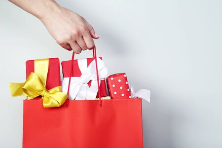 Female hand holding shopping bag with gift boxes on grey background 写真素材