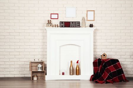 White fireplace with photo frames, christmas decorations and champagne bottles