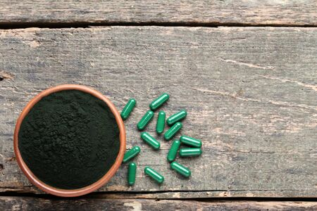 Spirulina powder and capsules on grey wooden table