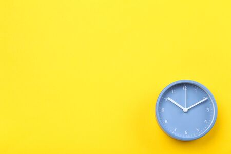 Blue round clock on yellow background